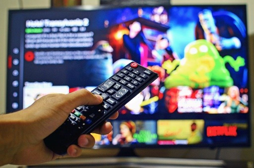hand pointing remote at TV showing Netflix