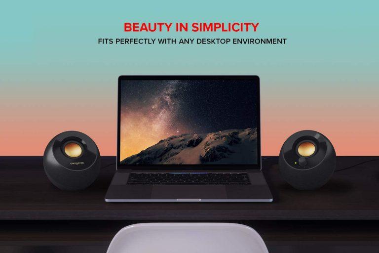Creative Pebble Plus 2.1 USB-Powered Desktop Speakers beside a laptop
