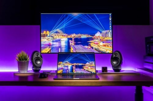 Speakers surrounding tv and laptop