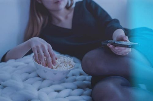 woman holding remote control and popcorn