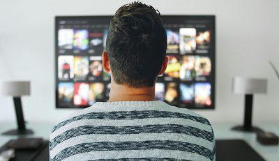 man facing flat screen TV