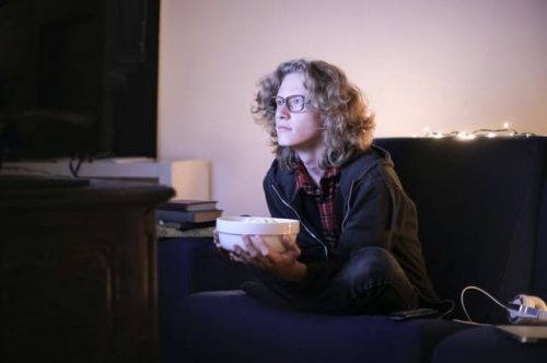 man watching tv with bowl of food