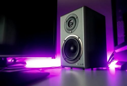 black speakers with violet light surrounding it