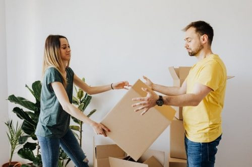 couple handing boxes to each other
