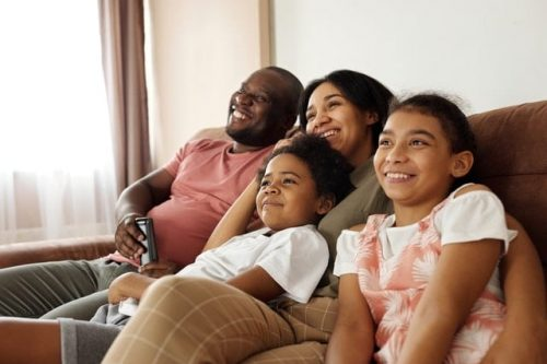 family of four looking at a TV not in sight