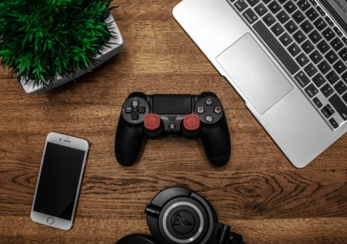 flat lay of plant, phone, laptop, headset and console controller on table