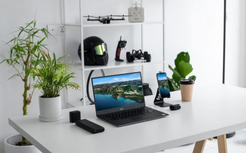 gadgets and plants on a white table