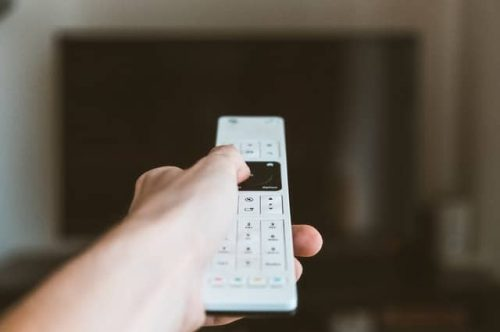 hand holding a white remote