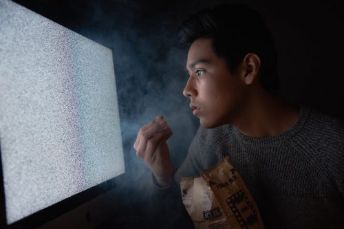 man eating chips while looking at TV