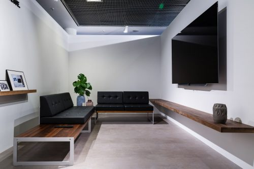 view of a living room with large TV and black sofas