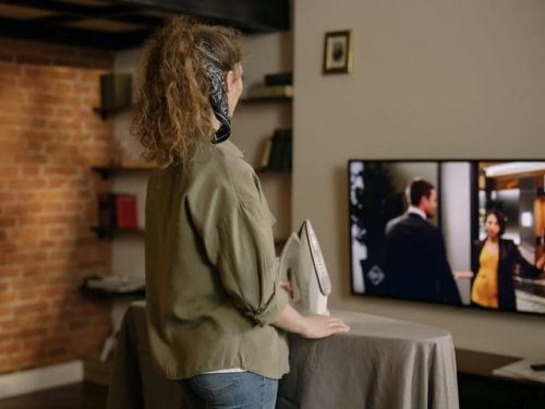 woman standing up while watching TV