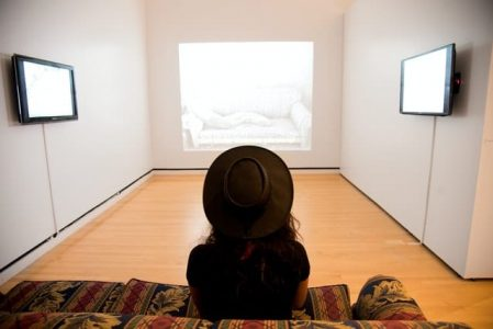 woman wearing hat facing the wall with projection in well-lit room