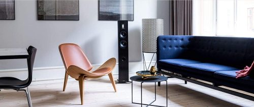 Piega Premium 501 Wireless Floor-Standing Speakers And Chairs In A Room