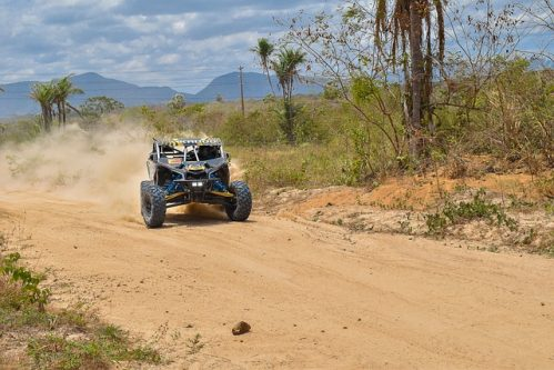 UTV running on a dirt road with dust behind it