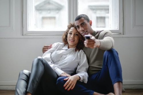 couple sitting on the floor while watching TV
