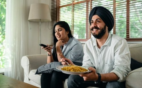 couple sitting on the sofa while holding remote and food