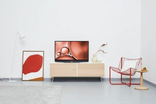 flat screen TV in between red painting and red chair