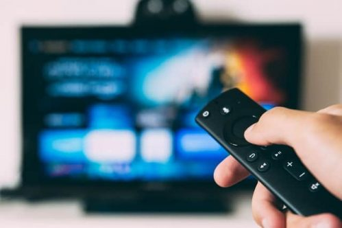 hand holding Fire TV remote towards set