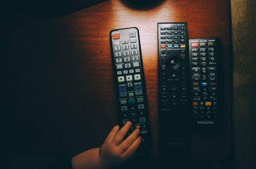 little hand holding one of the three remote controls on the table
