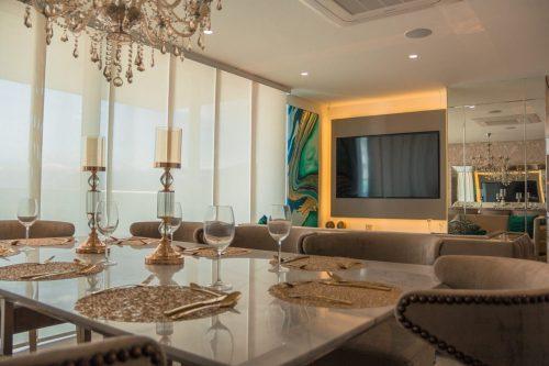 luxurious room with chandelier, wine glasses and a large TV