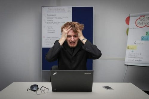 man in front of laptop putting hands on head out of frustration