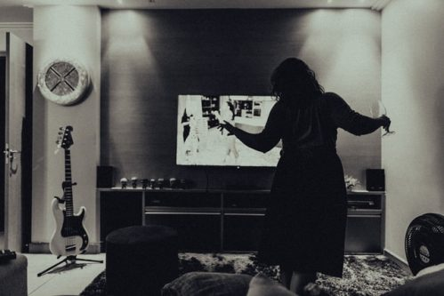 person standing up holding wine glass in front of TV