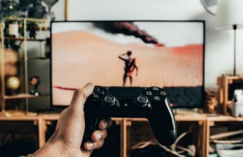 player holding PS4 controller in front of TV