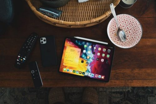 tablet, phone, remote control and mug on table
