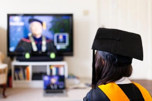 woman with graduation cap watching TV